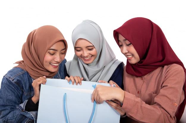 ショッピングバッグを開くと興奮するベールに包まれた女性