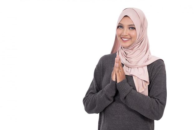 ようこそジェスチャーを示す笑みを浮かべてイスラム教徒の女性