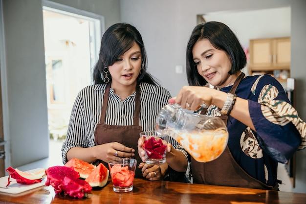 Женщина делает сладкий напиток из фруктов