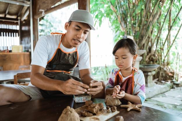 アジアの父と娘の粘土での作業