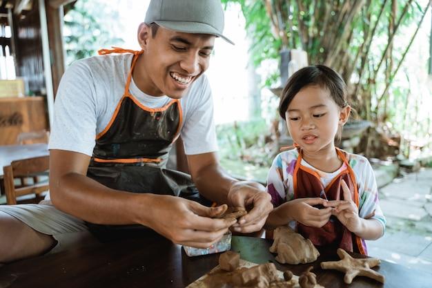 陶器を作る粘土で働く子供