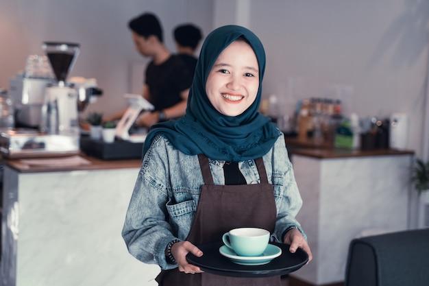 Мусульманский официант держит чашку кофе