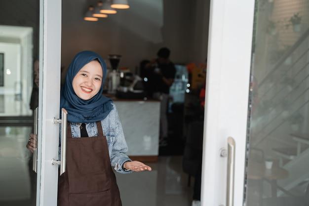 Дружелюбная азиатская красивая мусульманская женщина приветствует гостя в магазине