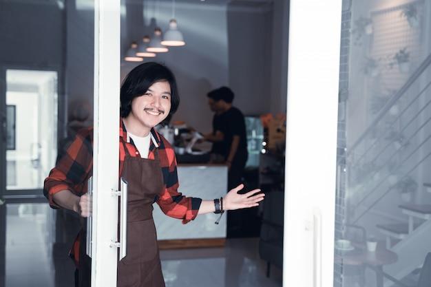 Бариста открывает дверь в своем кафе приветствуя