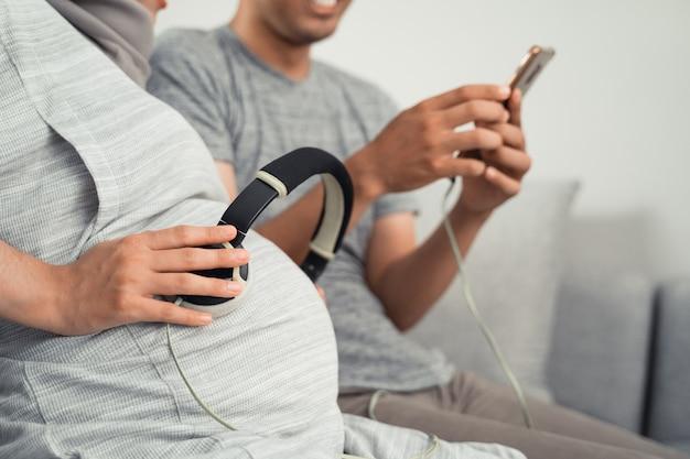 妊娠中の腹にイヤホンでクラシック音楽を聴く