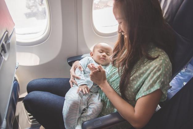 母親と赤ちゃんが飛行機の中で一緒に座っています。