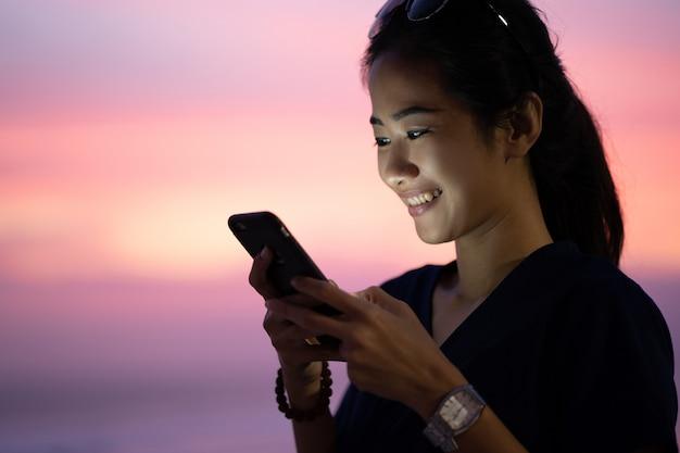 スマートフォンを使用して肖像若い女性