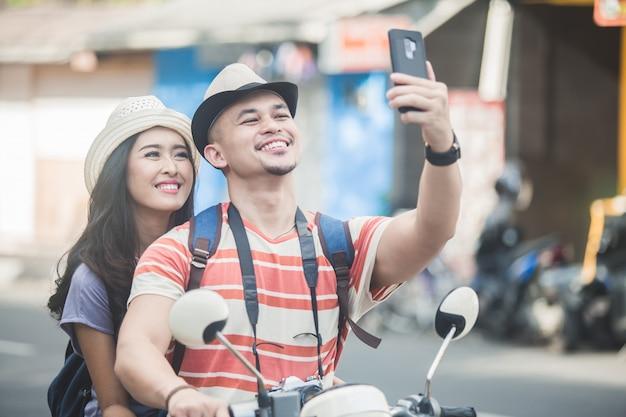 Две молодые туристы, делающие селфи с помощью камеры мобильного телефона