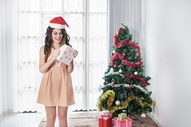 彼女のプレゼントを開くサンタさんの帽子をかぶっている美しいカジュアルな女性