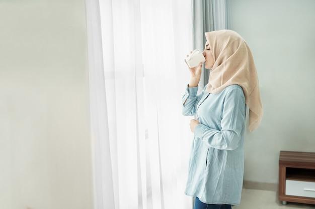 お茶を飲みながらヒジャーブを着ている美しい若い女性