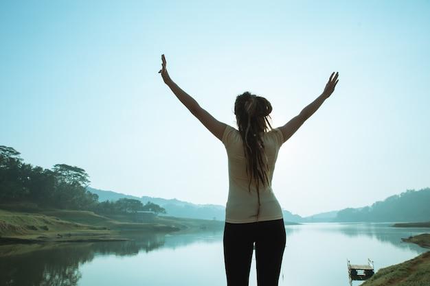Женщина наслаждается утром и поднимает руку