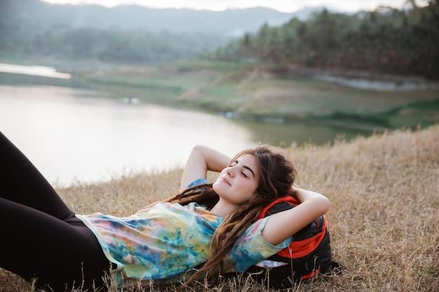 Красивая женщина лежит на траве и наслаждается путешествием
