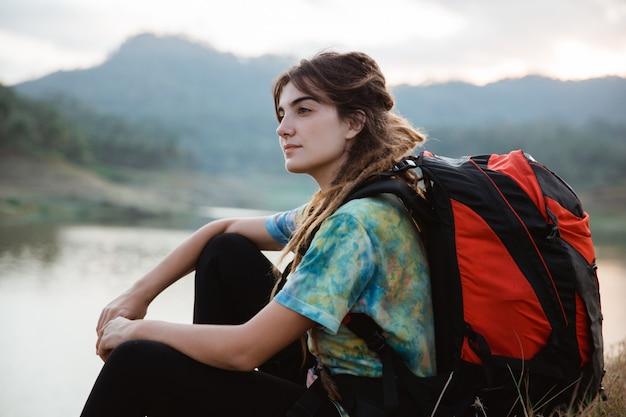 Закройте вверх по стороне озера кавказской женщины одной сидя