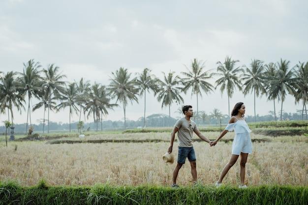 スタイリッシュな田んぼを一緒に歩くカップル