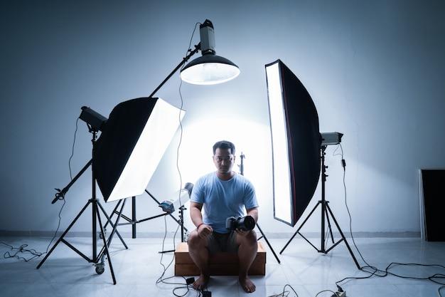 Мужской фотограф в фотостудии в окружении осветительного оборудования