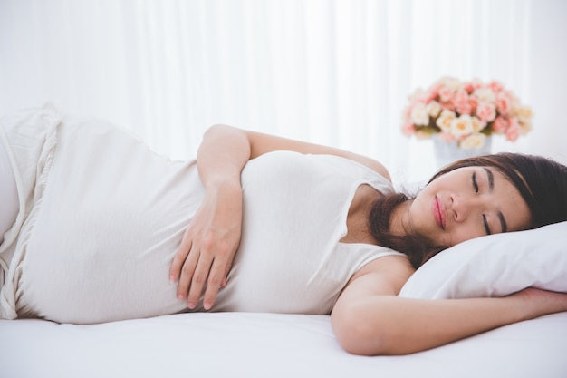 平和的に眠っている美しい妊娠中のアジア女性
