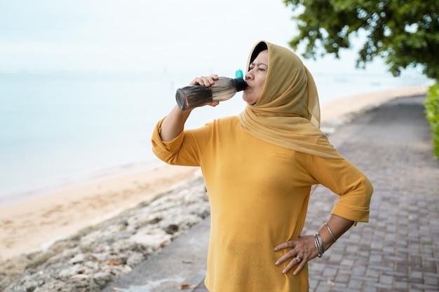 年配のイスラム教徒の女性は水を飲む