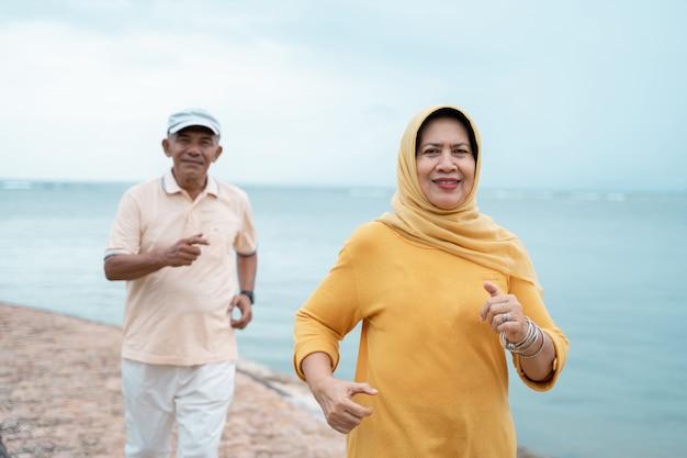 イスラム教徒の老夫婦のトレーニングとビーチで実行