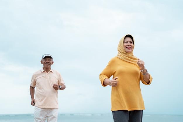 年配のカップルを実行して、屋外で運動