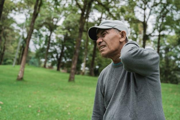 Старший азиатский мужчина имея боль в спине и шее