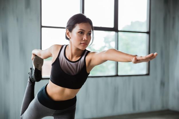 Растяжка спортивная женщина в спортивной одежде в помещении