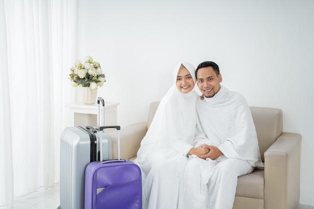 イスラム教徒のカップルは、ウムラの前に白い伝統的な服を着て座っています。