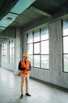 エンジニアは建物のプロジェクトサイトを検査しています