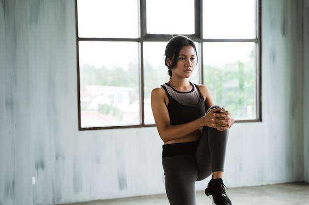 Женщина в тренажерном зале делает упражнения на растяжку