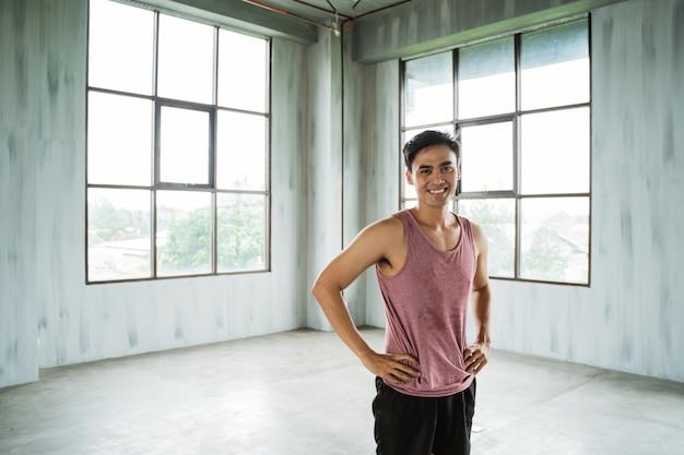 Позируют руки талии азиатского спортсмена, отдыхая после тренировки