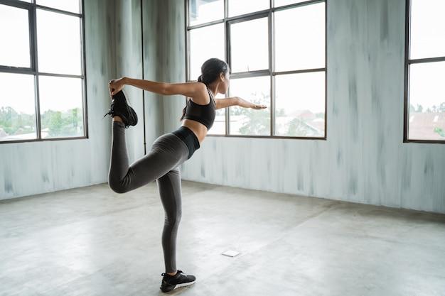 Активная женщина делает движения равновесия для вытянуть ноги