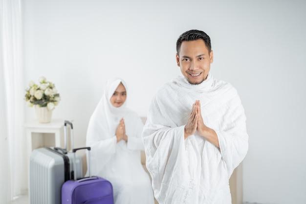 ウムラの前に彼の妻の前に立っているイスラム教徒の若い男