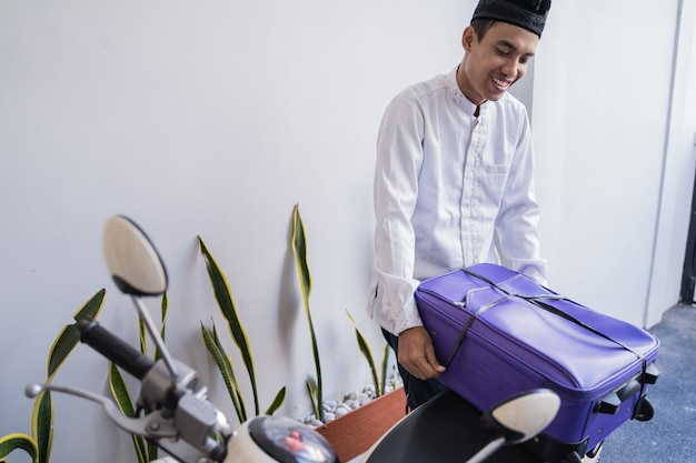 イスラム教徒の男性がスーツケースを運ぶイドゥルフィトリバリクカンポンムディクのオートバイに乗る