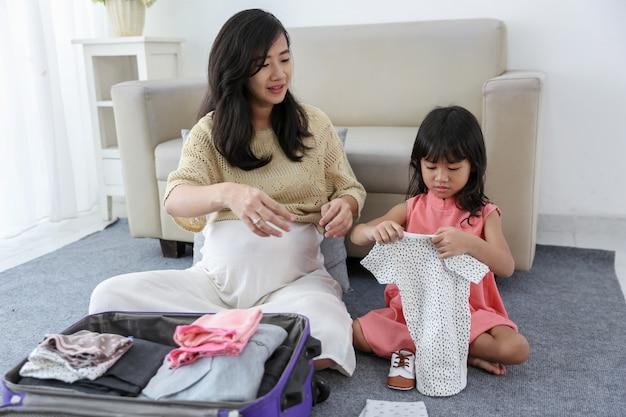Азиатская маленькая девочка держит детскую одежду и обувь