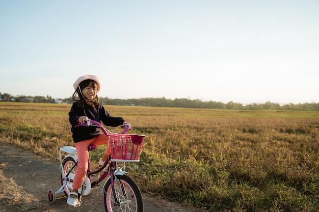 幼児は屋外で彼女の自転車に乗って楽しむ