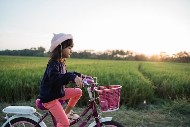 屋外に彼女の自転車に乗って喜んでいる子供女の子