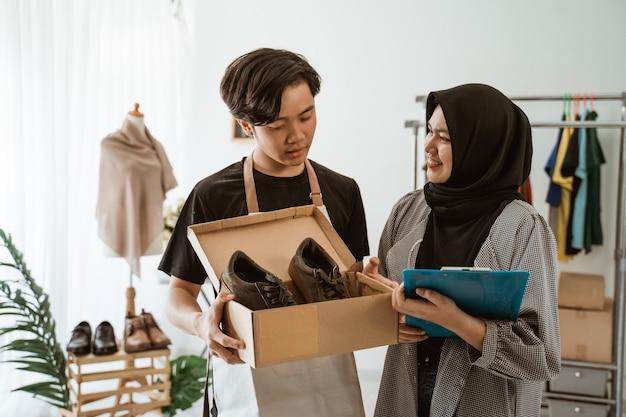 ヒジャーブとハンサムな男性が働いて若いイスラム教徒の女性