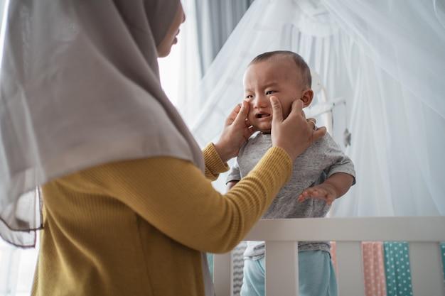 Мама пытается успокоить плачущего ребенка в кроватке
