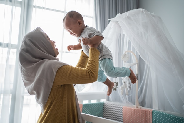 Азиатская мать носит ее ребенка