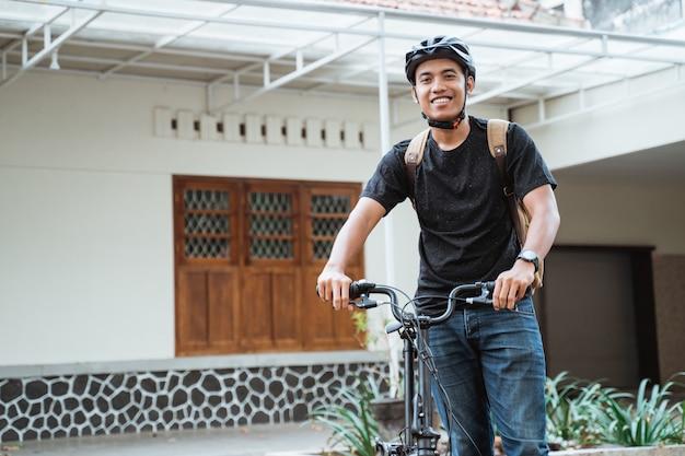Усмехаясь азиатский молодой человек стоя с складывая велосипедом