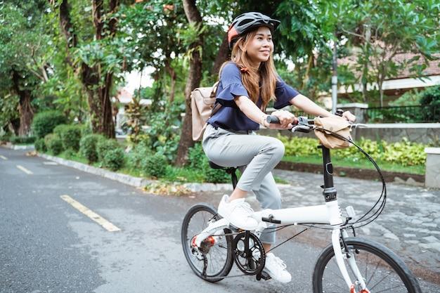 Азиатская молодая женщина идет носить шлем и сумку на велосипеде