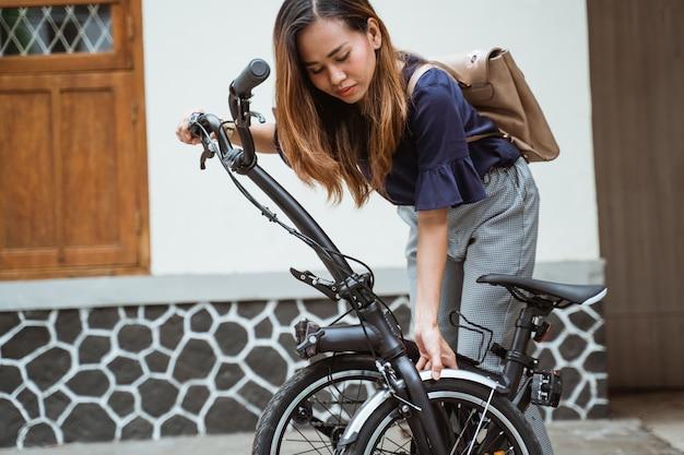 Молодая женщина готовит свой складной велосипед
