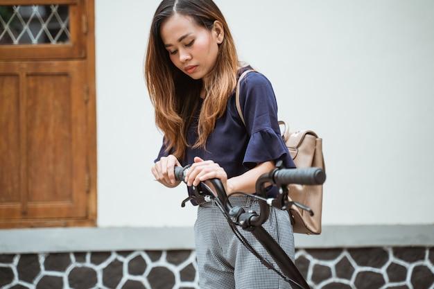 Азиатская молодая женщина пытается сложить складной велосипед, чтобы подготовиться пойти на работу