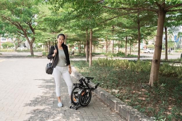 Работник женщины азиатский молодой стоя с ее складывая велосипедом