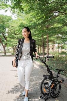 Усмехаясь работник женщины азиатский молодой стоя с ее складывая велосипедом