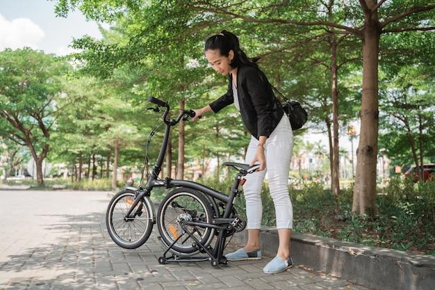 Азиатская женщина пытается сложить складной велосипед