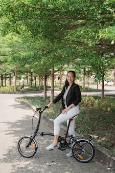 Работница готова кататься на своем складном велосипеде