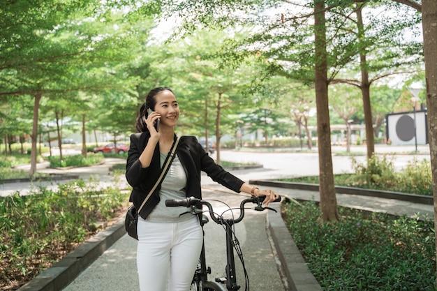 Улыбающаяся работающая женщина гуляет со своим складным велосипедом во время телефонного звонка