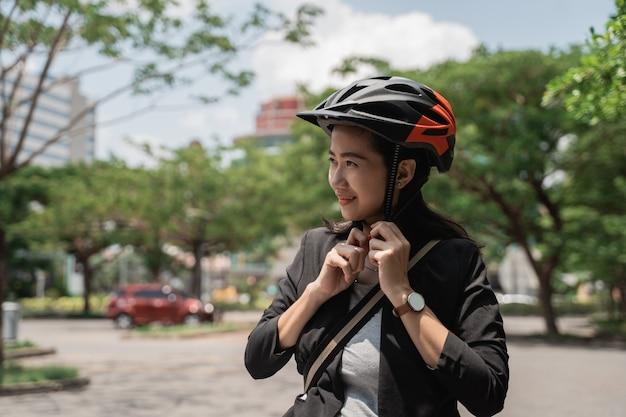 Велосипед шлема азиатской молодой женщины нося для безопасности