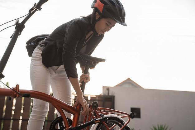 Азиатская женщина в шлеме и сумке готовит складной велосипед из дома к работе