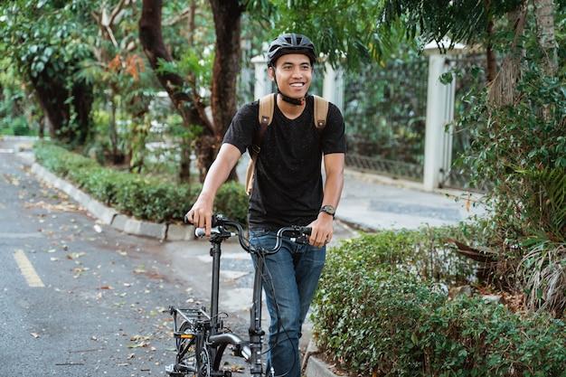 Усмехаясь азиатский молодой человек гуляя с складывая велосипедом